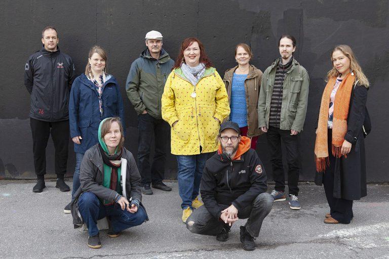 TOTEM-teatterin henkilökuntaa ulkovaatteissa mustan seinän edessä.